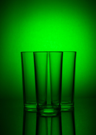 Three empty glasses on green background with reflection Stock Photo