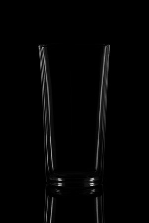 Empty glass on black background with reflection