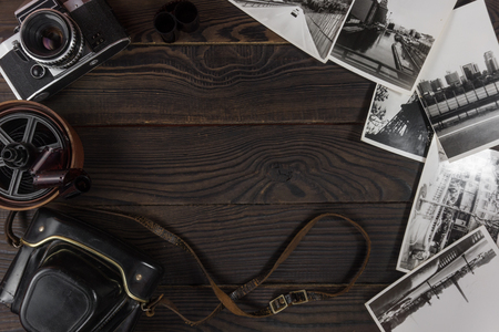specular: Old camera, acsessories and black and white photographs are on t