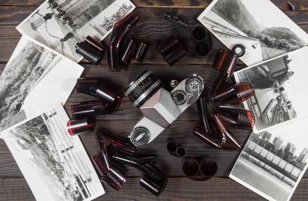 specular: Old camera, film and black and white photographs are on the dark Stock Photo