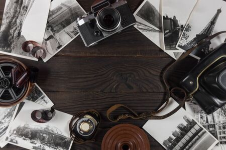 Old camera, acsessories and black and white photographs are on t