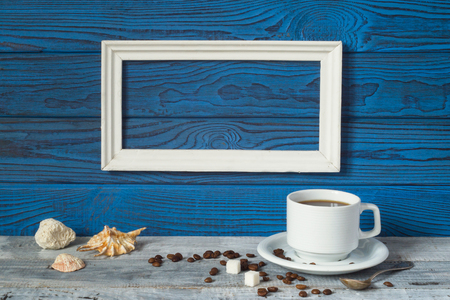 White frame, two coffee cups and a jug on a background of blue boards Stock Photo