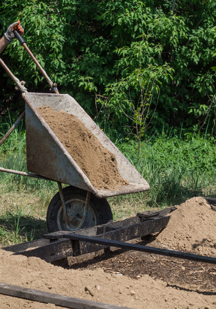 The man pours out the clay from the wheelbarrow