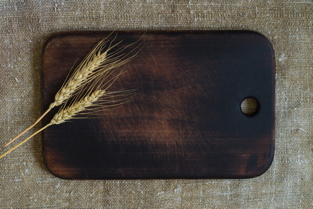 Wheat ears on a kitchen board on a sacking background