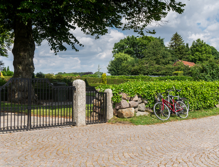 Red bicycle at the iron gate in the park Stock Photo