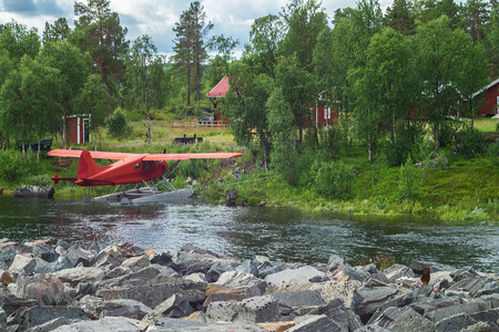 Little Red seaplane at the stony bank of the river, Sweden