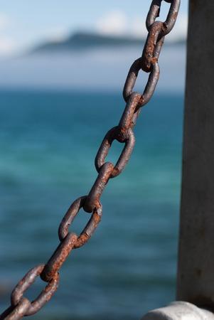 Rusty metal chain against a blue gulf