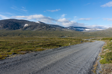 Dirt road jn background of snow-covered mountains in Jotunheimen National Park, Norway