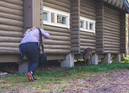 Girl photographs deer near a wooden house