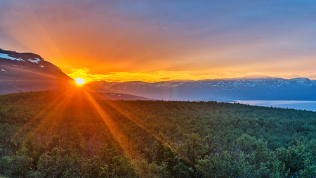 Midnight sun in summer in Abisko National Park, Sweden 免版税图像