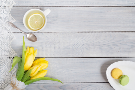 Yellow tulips, lemon tea and macarons on a white wooden table