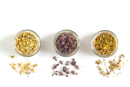 Medicinal herbs in glass jars on a white background
