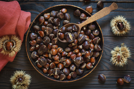 Roasted chestnuts in a pan and whole fruits