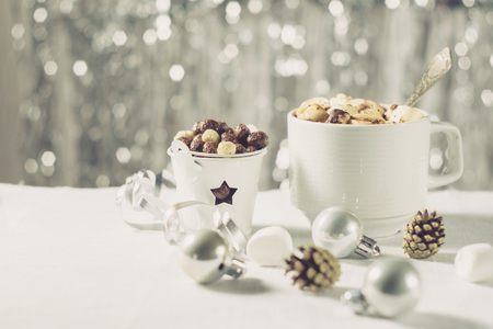 A cup of cocoa with marshmallows and corn balls in the New Year Christmas table setting on a shiny background