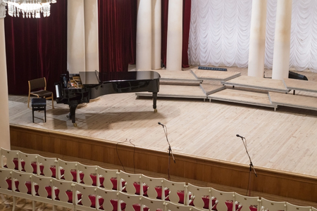 Piano on scene and empty chairs in auditorium of the philharmonic concert hall Stok Fotoğraf