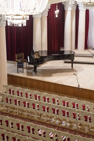 Piano on scene and empty chairs in auditorium of the philharmonic concert hall Stock Photo