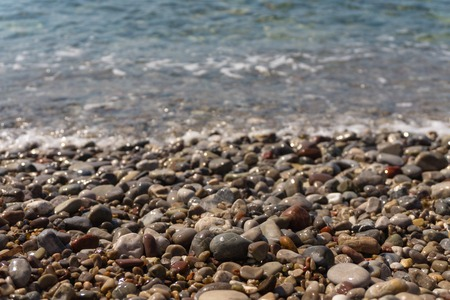 Colorful sea pebbles on the shore and clear water