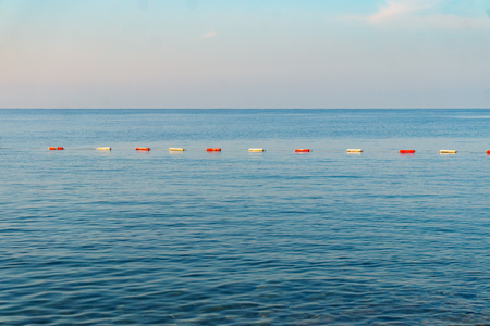 Row of red and white buoys in the blue sea