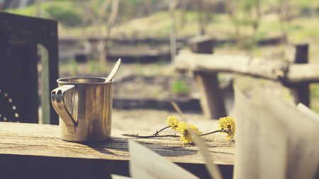 Metal mug, flowering branch and a book on a wooden table in the garden