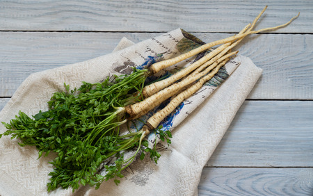 Bunch of parsley root with green leaves on a white wooden table Imagens