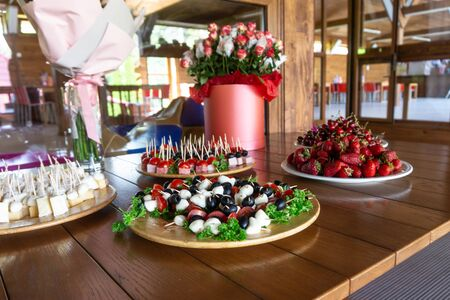 Snack plates with cheese, olives and strawberries on a buffet table 写真素材