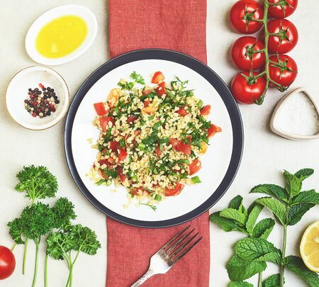 Lebanese traditional salad taboule with ingredients: parsley, mint, lemon, tomatoes, olive oil, salt and pepper on red napkin and white and black plate