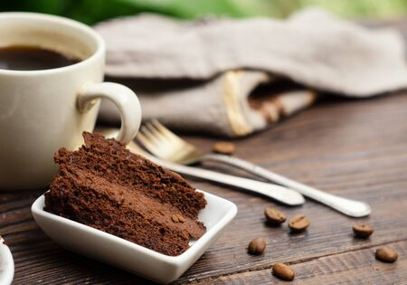 Home baked chocolate cake and a cup of coffee on a wooden table outdoors Stock Photo