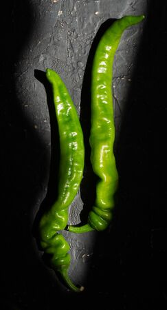 Two pods of green hot peppers on a dark stone background