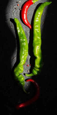Pods of green and red chili peppers on a black background Stock Photo