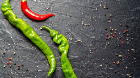 Pods of green and red chili peppers on a black textured background Stock Photo