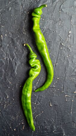 Two pods of green chili peppers on a dark background