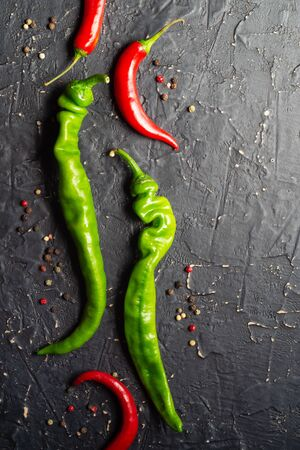 Pods of green and red hot peppers on a dark textured background Stock Photo