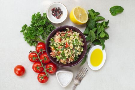 Lebanese traditional salad taboule soaked bulgur and ingredients-parsley, mint, lemon, tomatoes, olive oil, salt and pepper Stock Photo