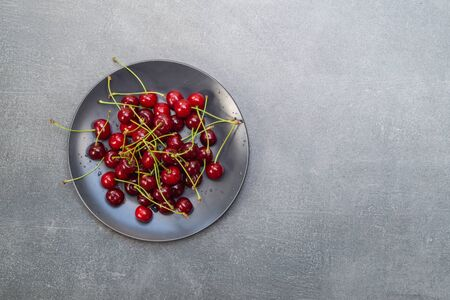 Red cherries in a black plate on a gray background. Top view Stock Photo