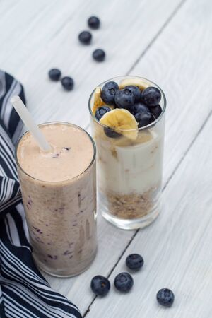 Banana, blueberry, oatmeal and yogurt smoothies and ingredients in two glasses on a white table. Healthy breakfast