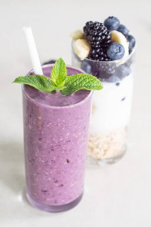Smoothies of banana, blueberry, blackberry, oatmeal and yogurt and ingredients in two glasses on a light background. Healthy breakfast