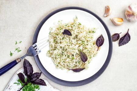 Rice in a white and black plates with herbs, basil and garlic on a white table. Top view