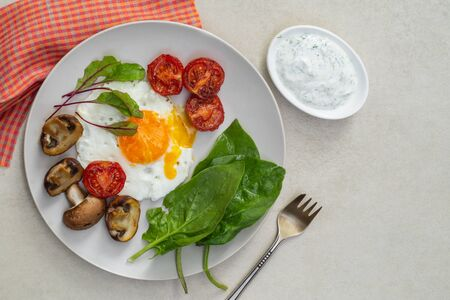 Nutritious breakfast of fried eggs, tomatoes, mushrooms with spinach, microgreen and sauce on a white plate
