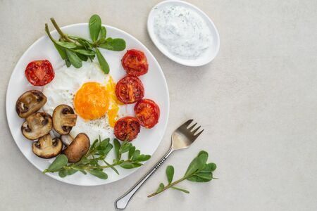 Nutritious breakfast of fried eggs, tomatoes, mushrooms with purslane and sauce on a white plate Zdjęcie Seryjne - 129249013