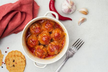 Meatballs stewed in tomato sauce in a saucepan, pepper and garlic on a white background