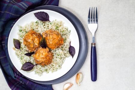 Meatballs and rice in a white and black plates with herbs and basil. Top view