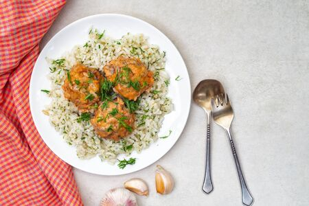 Stewed meatballs and rice in a white plate with herbs and garlic on a gray table. Top view