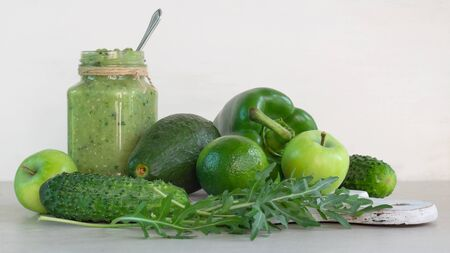 Green smoothie of apple, cucumber, avocado and pepper in a glass jar, whole ingredients on a white background Stock Photo