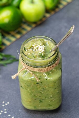 Vegetable green smoothie anh whole ingredients in a glass jar on a dark background Stock Photo
