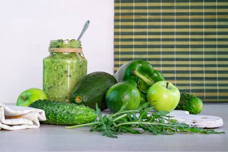 Green smoothie of apple, cucumber, avocado and pepper in a glass jar, whole ingredients on a white and striped background