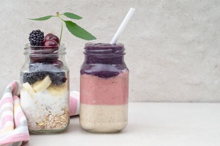 Layered cherry, banana and blackberry smoothie with yogurt and oatmeal and ingredients in two glass jars