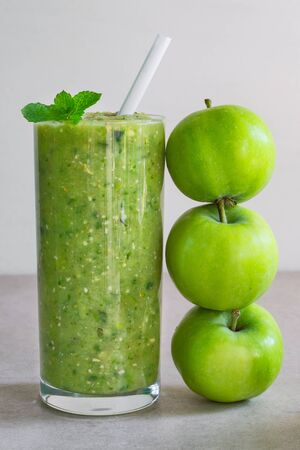 Green apple smoothie in a glass and three whole apples on a light background Stock Photo