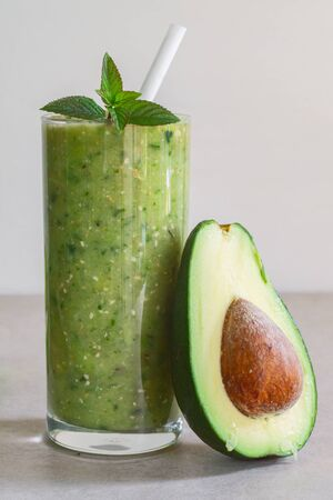 Green avocado smoothie in a glass and half avocado on a light background