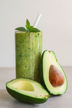 Green avocado smoothie in a glass, whole and half avocado on a light background Stock Photo