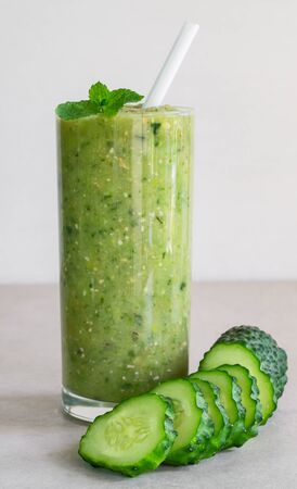 Green cucumber smoothie in a glass and sliced cucumber on a light background Stock Photo